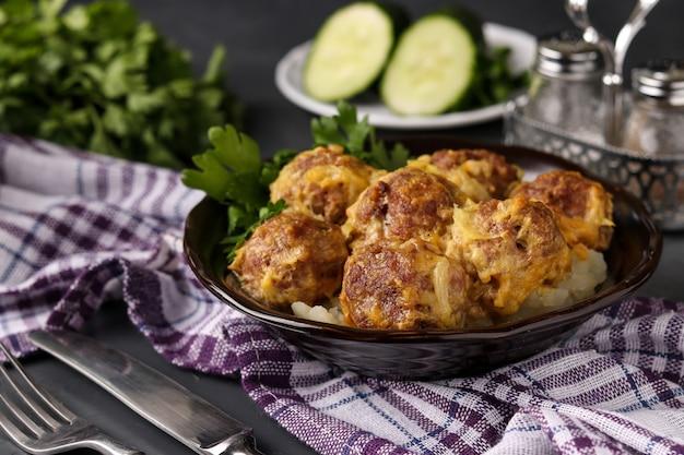 Fleischbällchen in currysauce in der schüssel vor einem dunklen hintergrund, horizontale ausrichtung