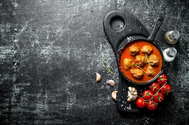 Fleischbällchen in einer pfanne mit tomaten und knoblauch. auf rustikal