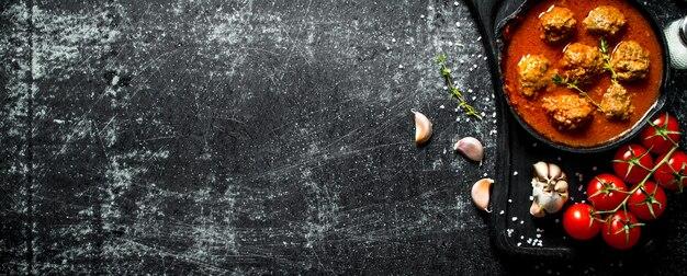 Fleischbällchen in einer pfanne mit tomaten und knoblauch. auf rustikalem hintergrund