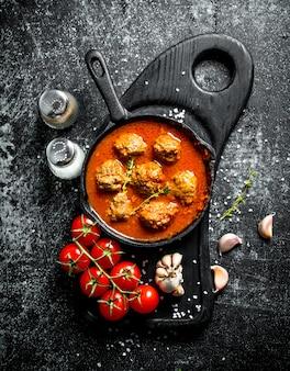Fleischbällchen in einer pfanne mit tomaten und knoblauch. auf rustikalem tisch