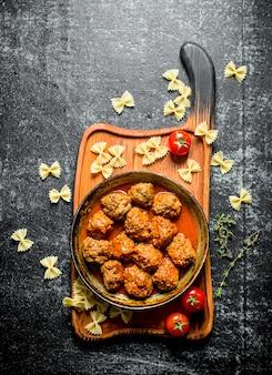 Fleischbällchen in pfanne und nudeln. auf rustikalem tisch