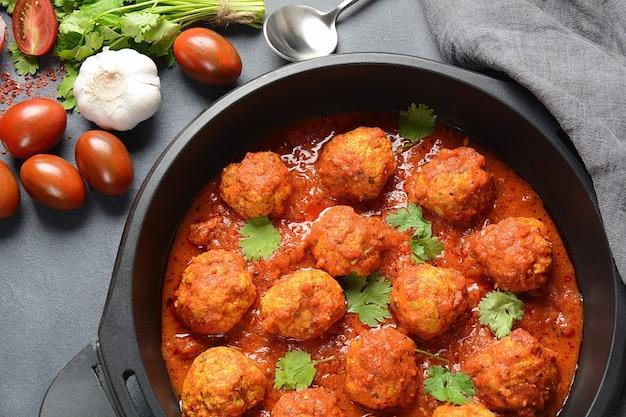Fleischbällchen in süß-saurer tomatensauce mit gewürzen in einer pfanne serviert
