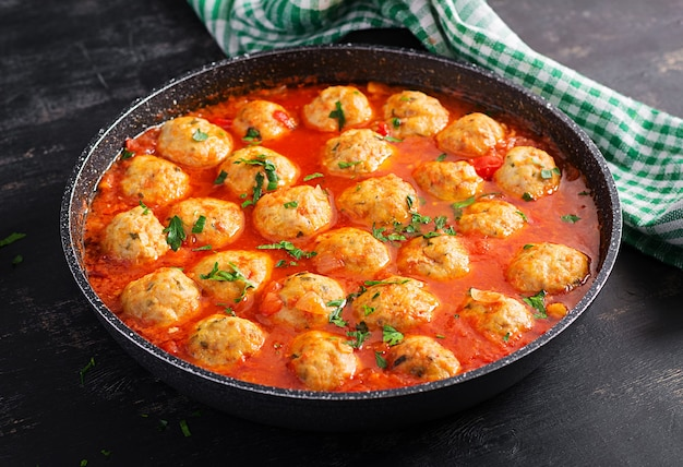 Fleischbällchen in tomatensauce in einer pfanne auf dunklem hintergrund.