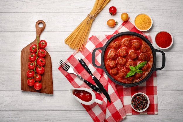 Fleischbällchen in tomatensauce mit gewürzen in einer pfanne und kirschtomaten auf einem schneidebrett