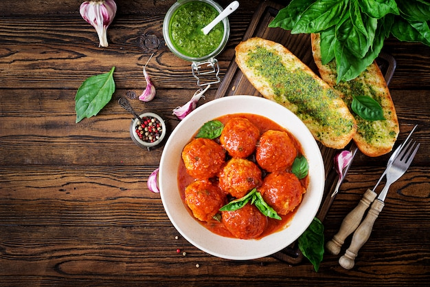 Fleischbällchen in tomatensauce und toast mit basilikumpesto. abendessen. leckeres essen. draufsicht flach legen