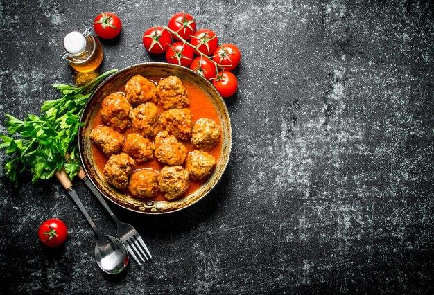 Fleischbällchen mit kräutern und tomaten. auf rustikal