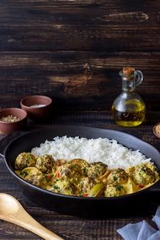 Fleischbällchen mit reis, currysauce, limette und rotem pfeffer. gesundes essen.
