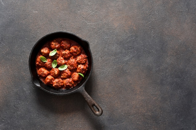 Fleischbällchen mit tomatensauce mit knoblauch und basilikum in einer pfanne auf einer braunen oberfläche.