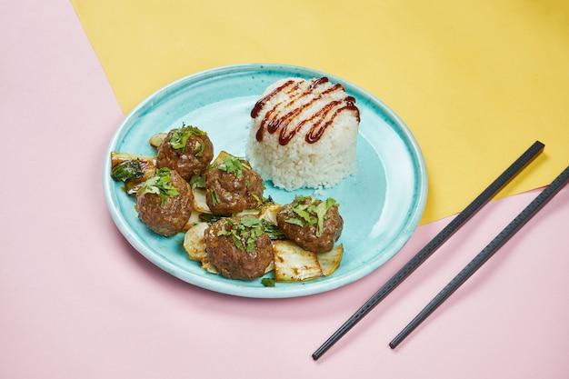 Fleischbällchen nach asiatischer art mit teriyaki-sauce, gebratenem kohl und reis in einem blauen teller auf farbiger oberfläche. schließen sie, kopieren sie platz für text