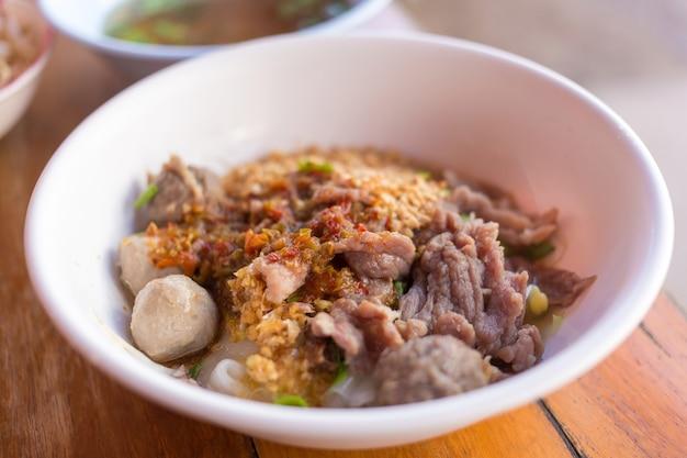 Fleischbällchen und fleisch mit breiten reisnudeln in der suppe wurde mit eingelegtem chili in einer weißen schüssel darüber gegeben