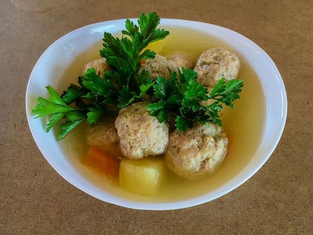 Fleischbällchen und kartoffeln in gemüsesuppe in einem weißen teller.