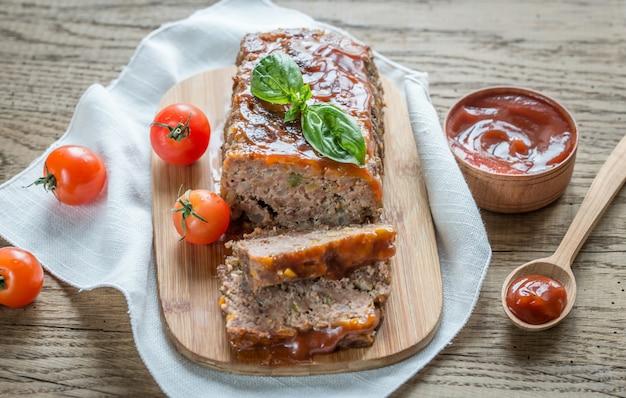 Fleischbrot mit barbecue-sauce auf dem holzbrett