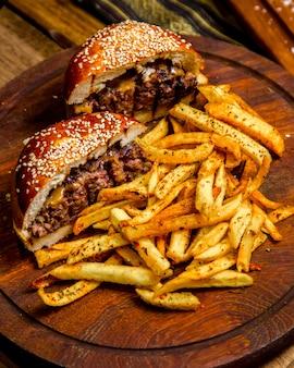 Fleischburger auf holzbrett pommes frites seitenansicht