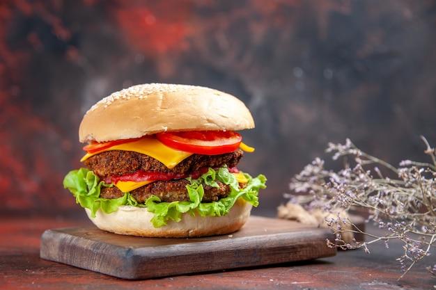 Fleischburger der vorderansicht mit käsesalat und tomaten auf dem dunklen hintergrund