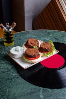 Fleischburger von oben auf dem fast-food-sandwich mit grünem tischessen