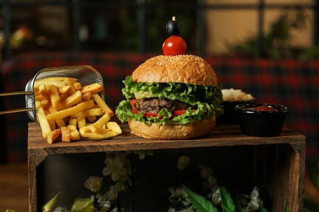 Fleischburger von vorne mit pommes frites ketchup und mayonnaise auf einem ständer