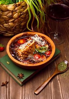 Fleischeintopf mit gemüse, tomaten. gulaschsuppe auf einem buch