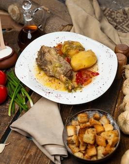 Fleischeintopf mit kartoffeln und öliger suppe in der weißen platte mit brotcrackern.