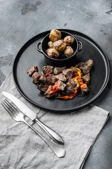 Fleischeintopf mit süßem paprika und lorbeerblatt auf grauem stein