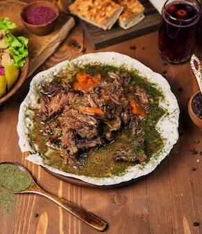 Fleischeintopf, turshu govurma mit zwiebeln, grünen kräutern, karotten in brühe-sauce