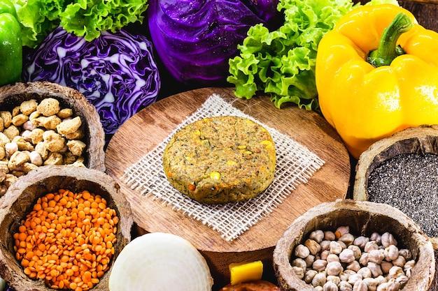 Fleischfreier veganer burger aus samen, gemüse, soja, kichererbsen, mais und litschi, umgeben von gemüse.