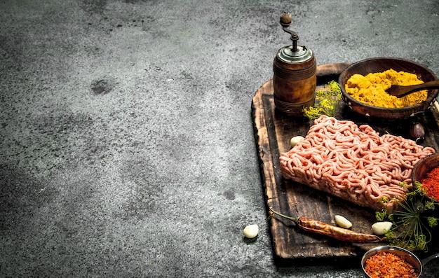 Fleischfüllung mit gewürzen und kräutern auf einem holzbrett. auf einem rustikalen hintergrund.