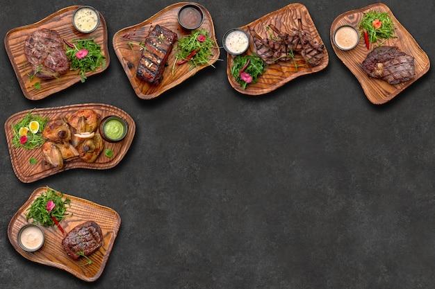 Fleischgerichte auf dunklem hintergrund mit platz für text