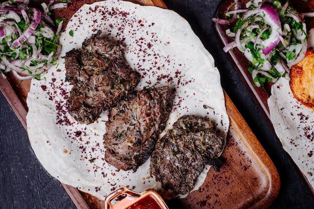 Fleischgrill in lavash mit zwiebelröllchen und sumakh.