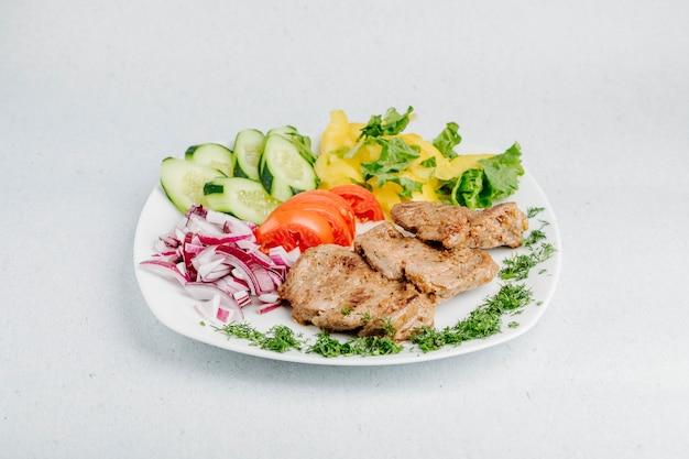 Fleischgrill mit gemüse und grünem salat.