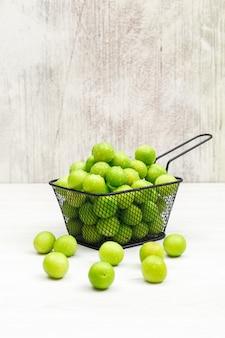 Fleischige grüne pflaumen in einem schwarzen sieb auf grunge und weiß. seitenansicht.