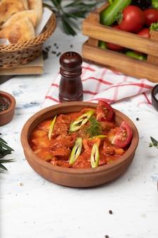 Fleischkartoffeleintopf mit tomatensauce und pfeffer in der tonwarenschüssel.