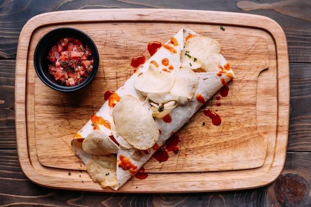 Fleischkebab mit den chips, die mit soße übersteigen und mit tomatensalat auf hölzerner platte gedient sind.