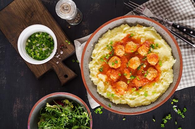 Fleischklöschen in der tomatensauce mit kartoffelpürees in der schüssel. ansicht von oben