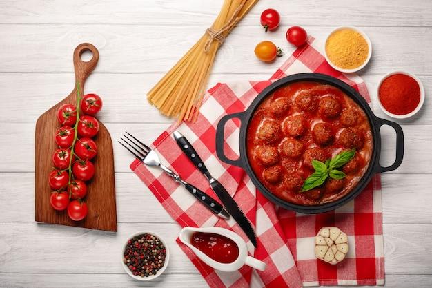 Fleischklöschen in tomatensauce mit gewürzen in einer bratpfanne und kirschtomaten auf einem schneidebrett und einem weißen holzbrett