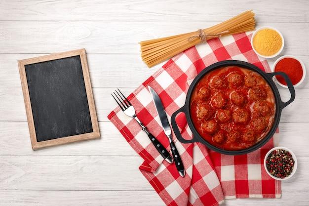 Fleischklöschen in tomatensauce mit gewürzen in einer pfanne auf einem weißen holzbrett