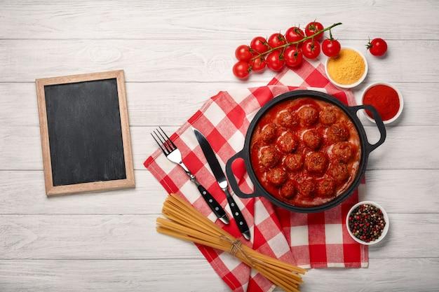 Fleischklöschen in tomatensauce mit gewürzen, kirschtomaten in einer bratpfanne auf einem weißen holzbrett
