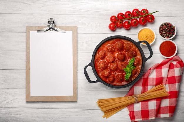 Fleischklöschen in tomatensauce mit gewürzen und basilikum in einer pfanne und kirschtomaten auf einem weißen holzbrett