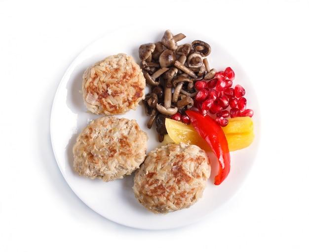 Fleischklöschen mit den reispilzen, gemüsepaprikas und granatapfelsamen lokalisiert auf weiß.