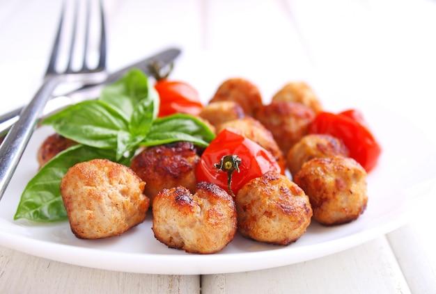 Fleischklöschen mit tomate in einem weißen teller auf einem weißen hintergrund. selektiver fokus.