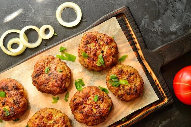 Fleischklößchen. schnitzel auf einem holzbrett. essen auf einem brett mit pergament. leckeres leckeres essen. draufsicht