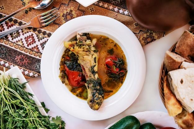 Fleischknochensuppe mit tomaten und kräutern.