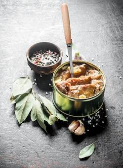 Fleischkonserven in einer dose mit knoblauch, gewürzen und lorbeerblatt auf dunklem rustikalem tisch