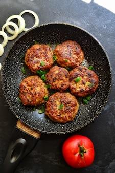 Fleischkoteletts. schnitzel in einer pfanne auf einem schwarzen betontisch. leckeres leckeres essen. draufsicht