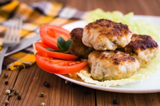 Fleischkoteletts und frischgemüse auf einem holztisch
