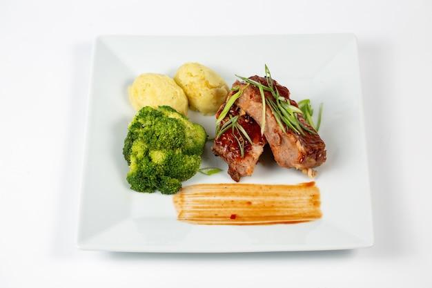 Fleischplatte mit barbecue-sauce kartoffelpüree und brokkoli
