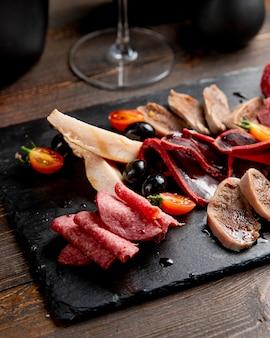 Fleischplatte mit oliven und tomaten