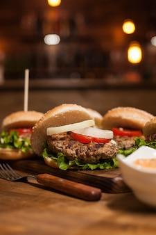 Fleischrindfleisch in leckeren burgern mit frischem salat im restaurant. gegrilltes fleisch. mittagessen essen.