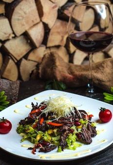 Fleischsalat mit bohnen und einem glas rotwein