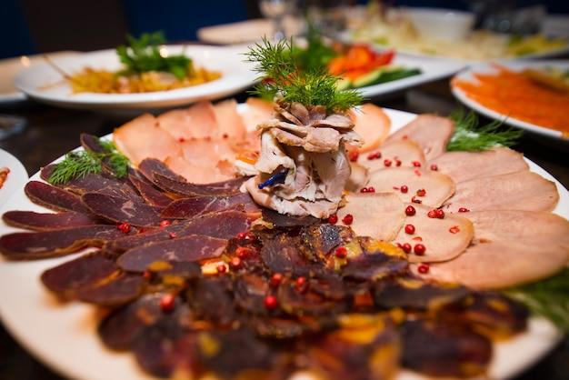 Fleischsnack auf einer platte auf dem hintergrund von tellern.