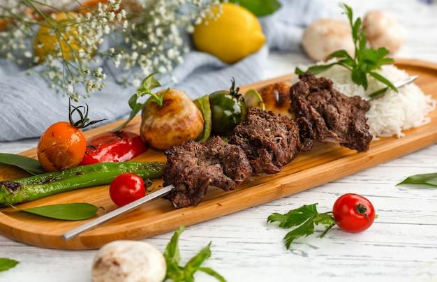 Fleischspieß mit gemüse und gekochtem reis